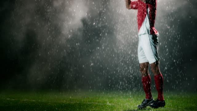 vidéos et rushes de slo mo poitrine de joueur de football piégeant la balle sous la pluie - sauter