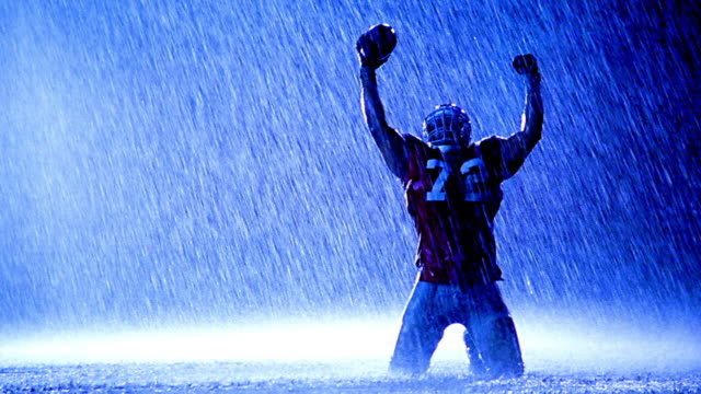vídeos de stock, filmes e b-roll de blue overexposed football player holding ball kneeling in rain with arms raised in victory - ajoelhando se