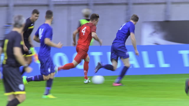 stockvideo's en b-roll-footage met football player in blue uniform outrunning his opponent at a match - sportwedstrijd
