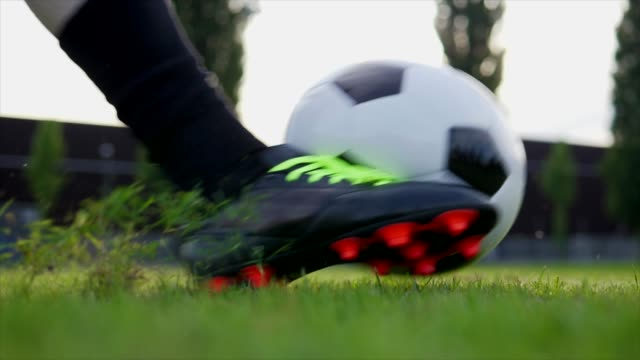 football player kicking ball on grass field at day - studded stock videos and b-roll footage
