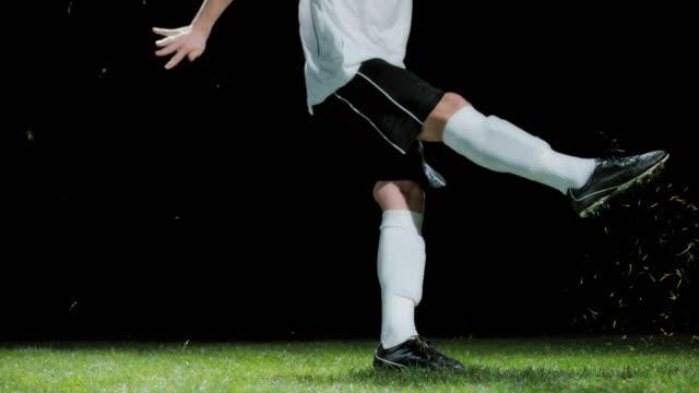 夜にボールを蹴るslo moサッカー選手 - 打つ点の映像素材/bロール