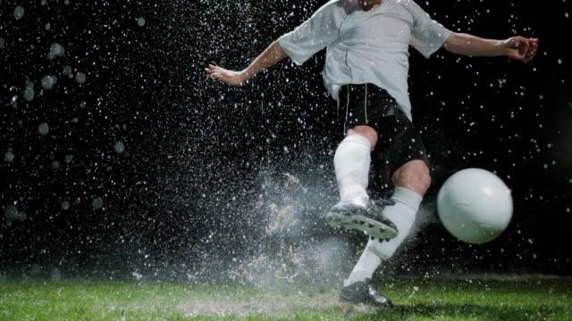 SLO MO Football player kicking the ball in rain