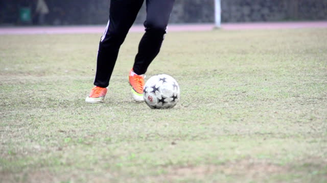 Football-Spieler treten den ball in Zeitlupe