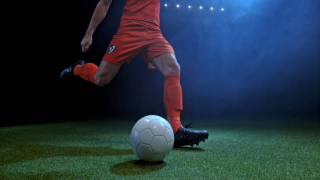 stockvideo's en b-roll-footage met speed ramp football player kicking the ball in the arena at night - schoppen lichaamsbeweging