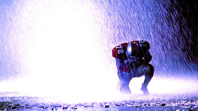 blue overexposed football player kneeling with head down in rain - kneeling stock videos and b-roll footage