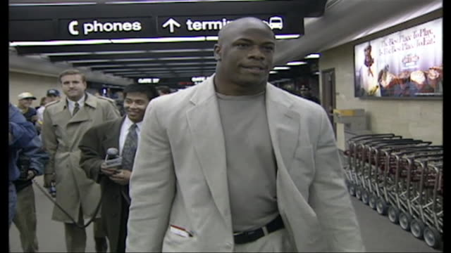 vidéos et rushes de football player lawrence phillips walks through airport in 1996. - nfc