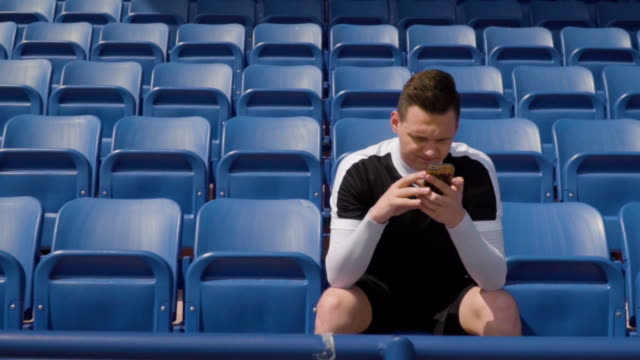 football player on an empty tribune and looks into the phone - stand stock videos & royalty-free footage