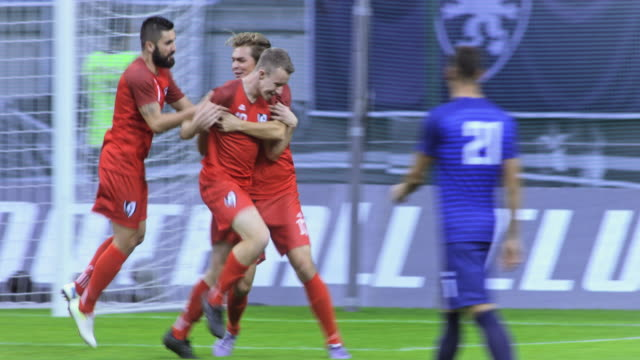 football player scoring a goal and celebrating with his teammates at a match - tor konstruktion stock-videos und b-roll-filmmaterial