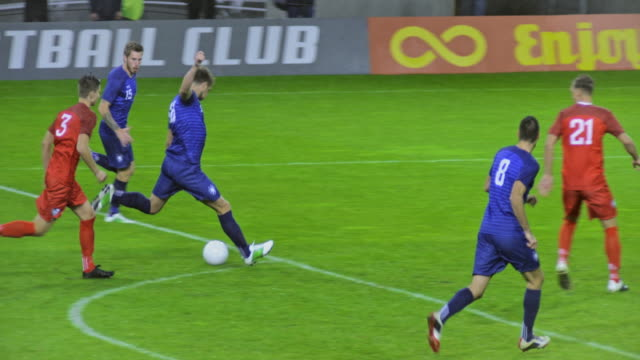 stockvideo's en b-roll-footage met slo mo football player shooting at the goal but the goalkeeper defends it - sportwedstrijd