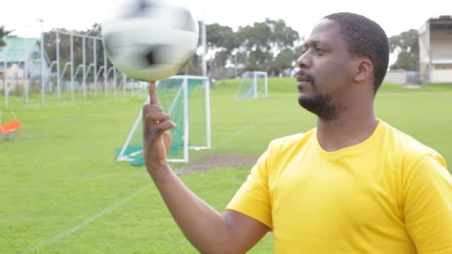 vídeos de stock e filmes b-roll de jogador de futebol de fiação uma bola no dedo - ditado