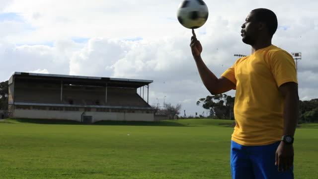 vídeos de stock, filmes e b-roll de jogador de futebol de spinning uma bola em seu dedo - brasileiro pardo