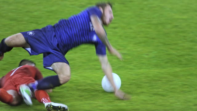 vídeos de stock, filmes e b-roll de slo mo football player tackling the opponent - futebol