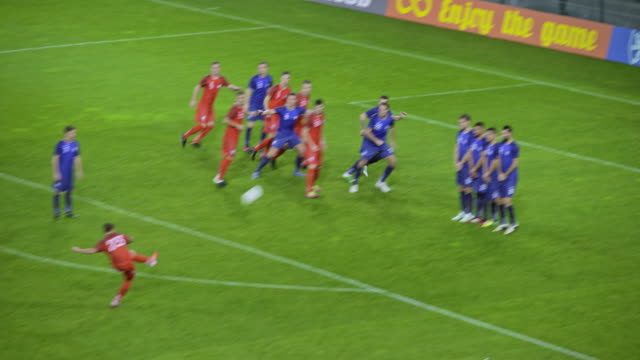 vidéos et rushes de football player takes a direct free kick but misses the goal - cage