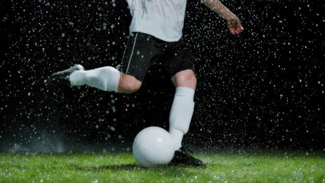 slo mo football player taking a free kick in heavy rain - インパクト点の映像素材/bロール