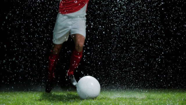 slo mo football player taking a free kick in rain - pitch stock videos & royalty-free footage