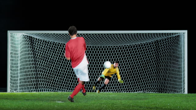 slo mo football player taking a penalty kick - goalkeeper stock videos & royalty-free footage