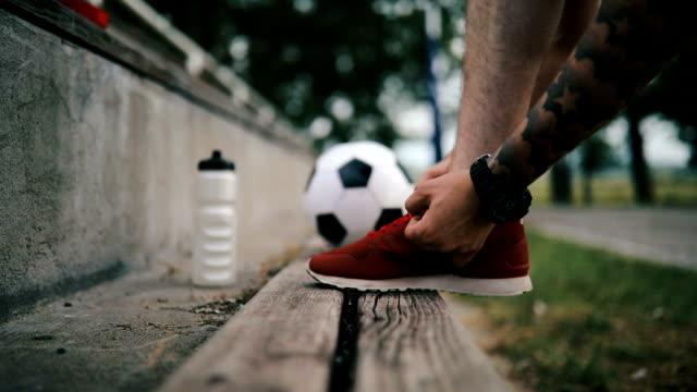 vídeos de stock, filmes e b-roll de jogador de futebol, amarrando o tênis de futebol - laço acessório