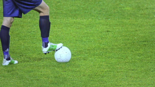 slo mo football player with one foot on the ball - football pitch stock videos and b-roll footage