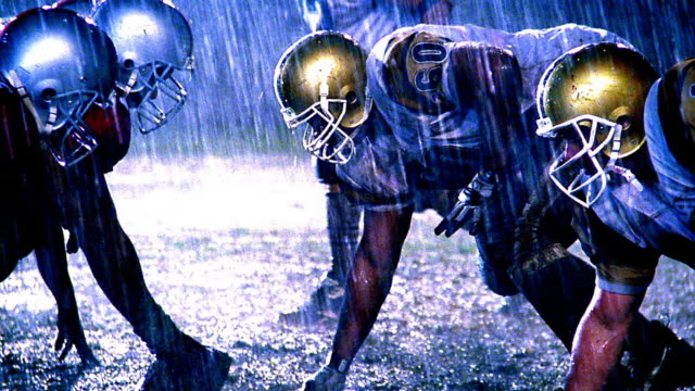 OVEREXPOSED football players at line of scrimmage, ball is snapped, players block each other / rain