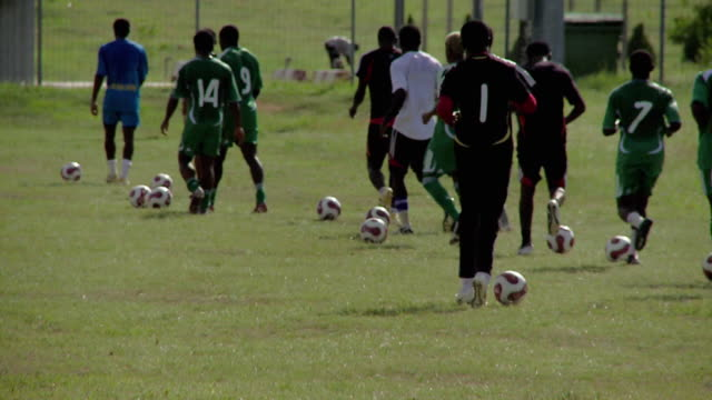 football players dribble balls across a field. available in hd. - nigeria stock videos and b-roll footage