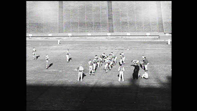 vídeos y material grabado en eventos de stock de football players practicing on the field of an empty stadium under the sun - 1940 1949