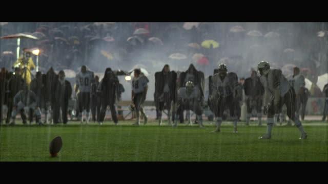 ws pan football players running after the kickoff and tackling - cheerleader stock videos & royalty-free footage