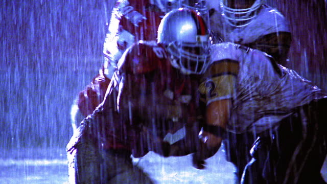 OVEREXPOSED football players tackling player carrying ball in rain