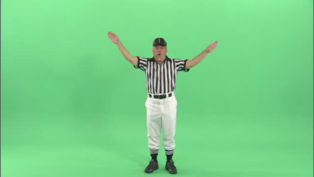 ws, football referee blowing whistle and signaling a discretionary or injury time out / studio, portrait - riposarsi video stock e b–roll