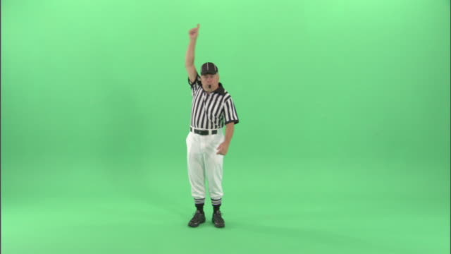 WS, Football referee blowing whistle and signaling to start the game clock / studio