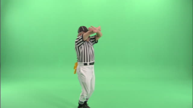 WS, Football referee blowing whistle and signaling to stop the game clock / studio