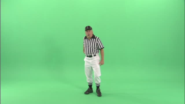 WS, Football referee blowing whistle and throwing yellow flag  in studio