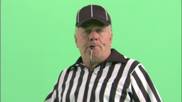 CU, Football referee blowing whistle in studio, portrait