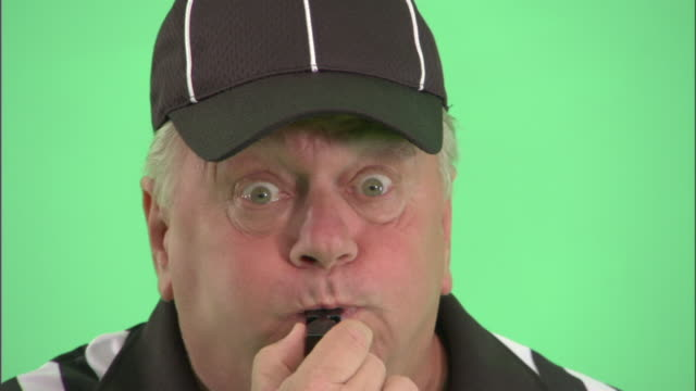 ecu, football referee blowing whistle in studio, portrait - trillerpfeife stock-videos und b-roll-filmmaterial