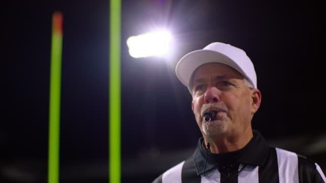 ms la slo mo football referee blowing whistle on field during game at night - trillerpfeife stock-videos und b-roll-filmmaterial