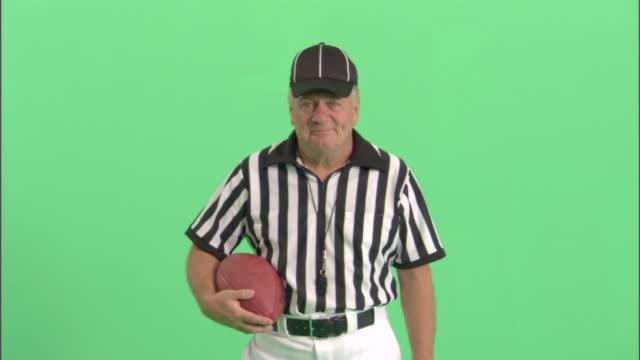 MS, Football referee holding football in studio, portrait