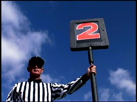 vidéos et rushes de football referee holding second down marker - un seul homme d'âge moyen