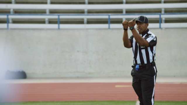 MS SLO MO. Football referee makes hand gestures from sideline.
