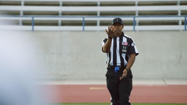 vidéos et rushes de ms slo mo. football referee makes juggling hand gestures signaling incomplete pass due to lack of possession inbounds. - un seul homme d'âge moyen