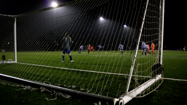 football / soccer goal scored from behind the goalposts (night) - scoring a goal stock videos and b-roll footage