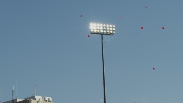 football stadium lights shine as balloons float into the sky. - nebraska stock videos & royalty-free footage