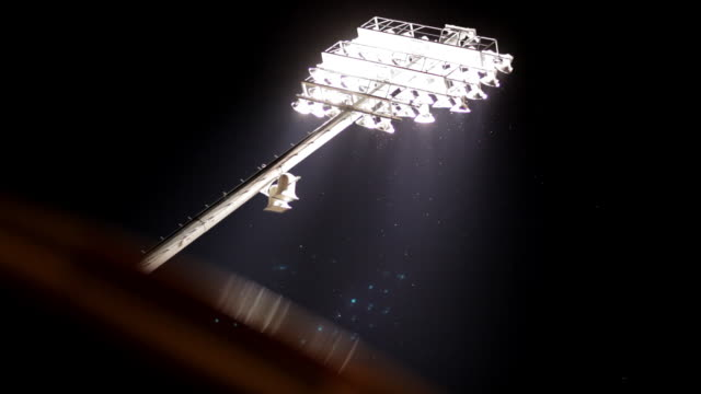football stadium lights shine in the dark sky surrounded with flying insects. - アメリカンフットボール場点の映像素材/bロール