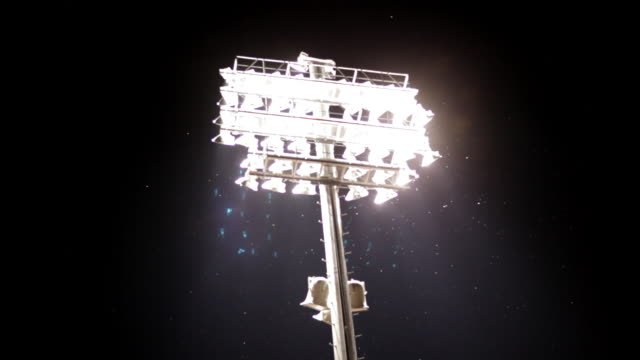 football stadium lights shine in the dark sky. - floodlight stock videos & royalty-free footage