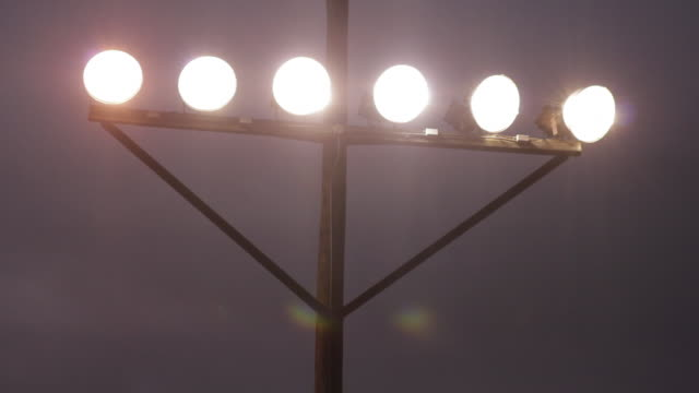 football stadium lights, six lights on a bar attached to a pole close - floodlight stock videos & royalty-free footage