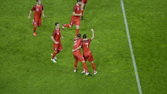 football team celebrating a goal at a match - aspirations点の映像素材/bロール