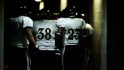 A football team in a circle gets pumped-up in the tunnel before the game