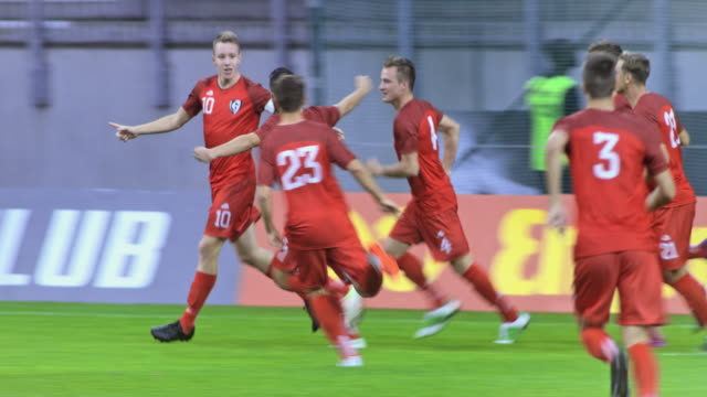 stockvideo's en b-roll-footage met football team in red uniforms scoring and celebrating - sportwedstrijd