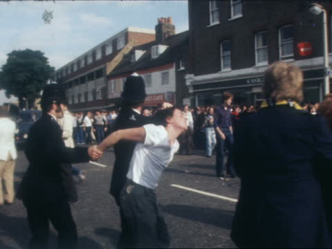 football violence; england: london: tottenhamextpolice and fans on streetpolice run down underground stepsambulanceyouth led off by two policemen. - violence stock videos & royalty-free footage