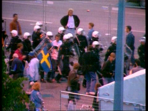 stockvideo's en b-roll-footage met football violence sweden stockholm tgv english supporters chasing swedish supporters outside stadium tlms english fans kicking swedish youth as he... - 1992