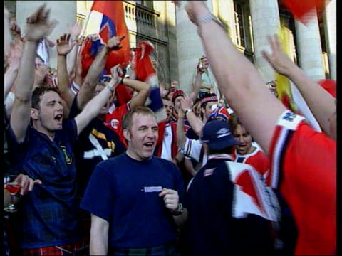 world cup 1998: scotland and norway draw; itn france: bordeaux: ext scotland fans singing and drinking on steps of building scotland and norwegian... - international team soccer stock videos & royalty-free footage