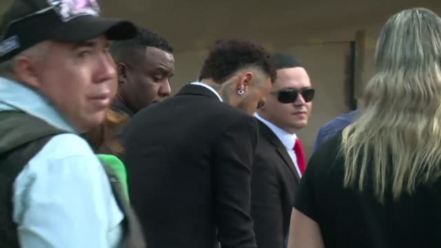 footballer neymar arrives at a police station to undergo questioning over an allegation of rape as a handful of supporters cheer him on - manciata attività video stock e b–roll